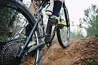 Close-up of mountainbiker on forest trail - JRFF00999