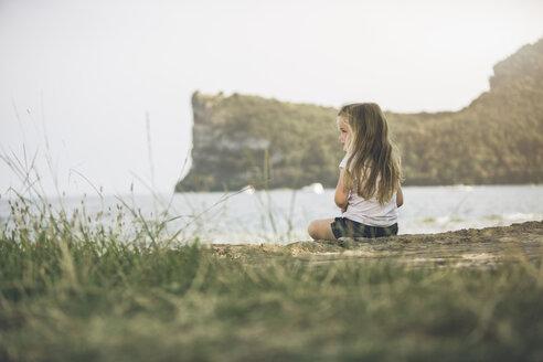 Italy, Lake Garda, girl sitting at lakeshore - SBOF00255