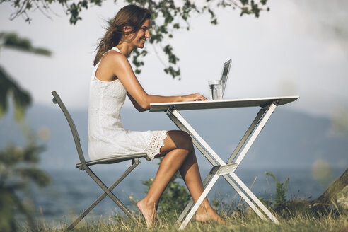 Italy, Lake Garda, young woman sitting at table with laptop - SBOF00264