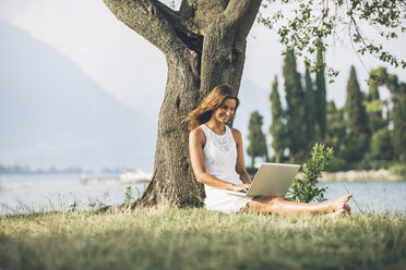 Italy, Lake Garda, young woman leaning against a tree using laptop - SBOF00267