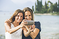 Italy, Lake Garda, two young women taking a selfie - SBOF00273
