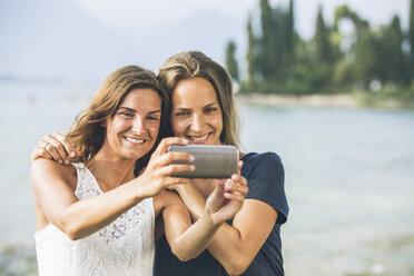 Italy, Lake Garda, two young women taking a selfie - SBOF00273