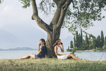 Italy, Lake Garda, two young women leaning against a tree talking on cell phones - SBOF00276