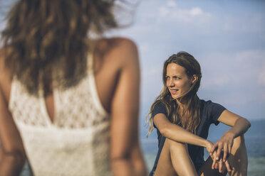 Italy, Lake Garda, two young women sitting at lakeshore - SBOF00279