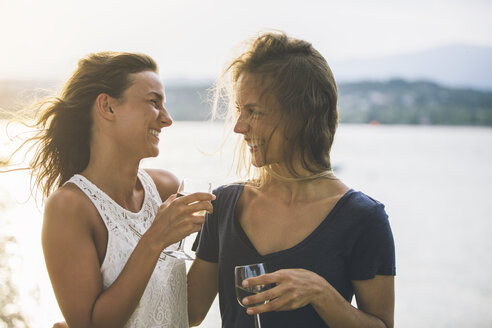 Italy, Lake Garda, two happy young women at lakeshore with glass of wine - SBOF00282