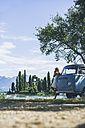 Italy, Lake Garda, young woman drinking coffee at camping bus - SBOF00288