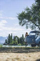 Italy, Lake Garda, young woman drinking coffee at camping bus - SBOF00288