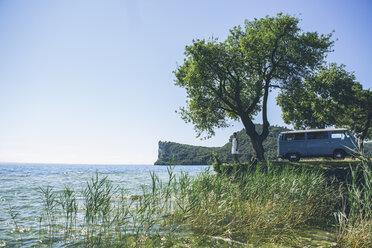 Italy, Lake Garda, woman with camping bus at lakeshore - SBOF00294