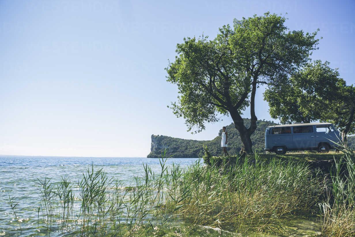 Italy, Lake Garda, woman with camping bus at lakeshore - SBOF00294 - Steve Brookland/Westend61
