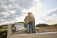 Couple standing on pick up truck with beer bottles - FMKF03164