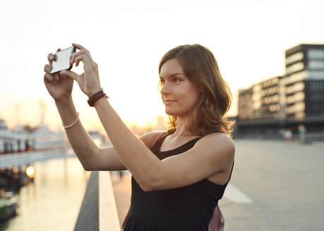 Germany, Young woman in Hamburg taking pictures with her smart phone - WHF00007