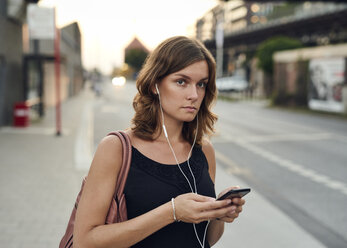 Germany, Young woman with smart phone exploring Hamburg - WHF00013
