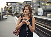 Germany, Young woman with smart phone exploring Hamburg - WHF00016