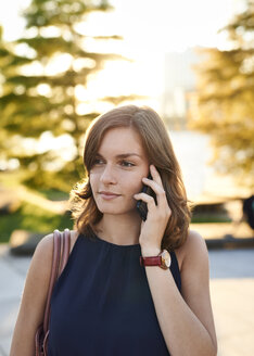 Germany, Hamburg, Young businesswoman talking on the phone - WHF00022