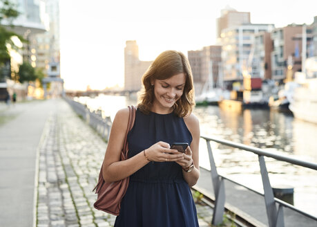 Germany, Young woman with smart phone exploring Hamburg - WHF00025