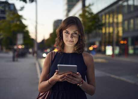 Germany, Hamburg, Young woman in the street using digital tablet - WHF00034
