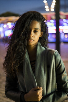 Portrait of a young woman on a funfair at night - KKAF00038