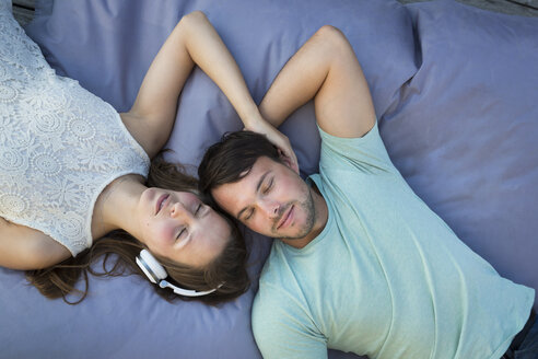 Young couple in love relaxing together on beanbag - JTLF00123