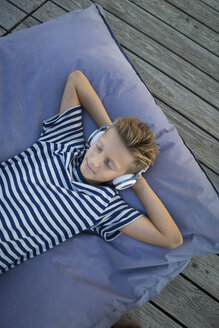 Boy lying on beanbag listening music with headphones - JTLF00126
