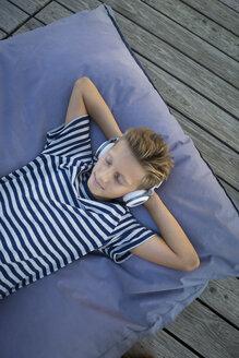 Boy lying on beanbag listening music with headphones - JTLF00126