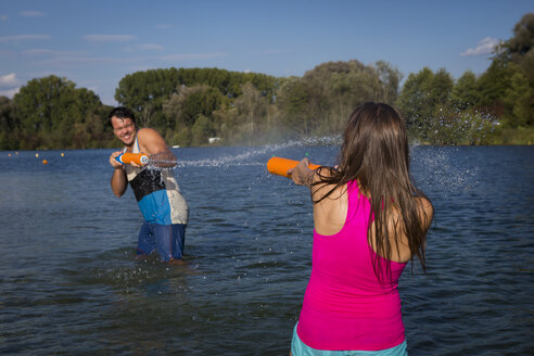 Young couple standing in at lake playing with water guns - JTLF00132