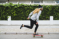 Young woman skateboarding on street - KKAF00058