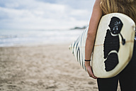 Woman with surfboard on the beach, partial view - KKAF00061
