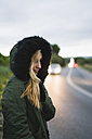 Young woman wearing hooded jacket waiting at roadside in the evening - KKAF00070