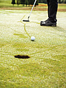Golfer on golf course with dew, partial view - LAF01774