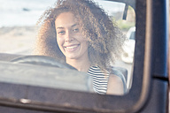 Portrait of smiling young woman sitting behind windscreen in a car - SIPF01055