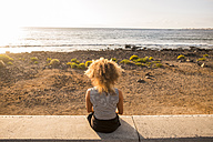 Back view of woman sitting on a wall looking at the sea - SIPF01076