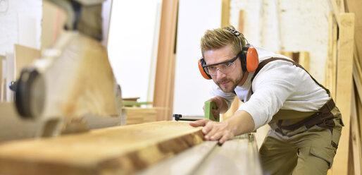Carpenter using sawing machine in his workshop - LYF00660