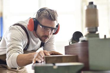 Carpenter using belt sander in his workshop - LYF00666