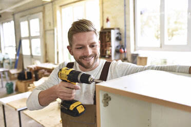 Carpenter assembling furniture in his workshop - LYF00681