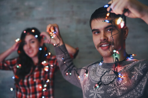 Young man holding fairy lights while his girlfriend watching in the bachground - RTBF00515