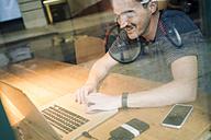 Man using laptop at desk - GIOF01594