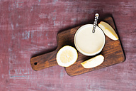 Glass of banana smoothie with apple and lemon on wooden board - MYF01834