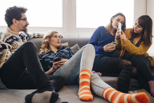 Four friends with smartphones on couch in living room hanging out - LCUF00076