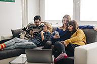 Four friends with smartphones on couch in living room hanging out - LCUF00082
