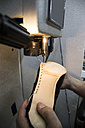 Shoemaker sewing the sole of a shoe using a machine in his workshop - ABZF01473