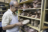 Shoemaker selecting shoe soles from a shelf in his workshop - ABZF01482