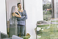 Smiling couple with dog standing at terrace door - MADF01203