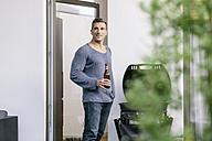 Smiling man with beer bottle standing at terrace door - MADF01209