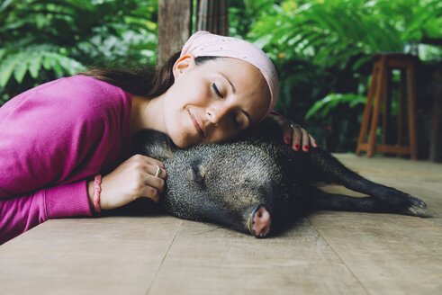 Peru, Woman cuddling domesticated peccary - GEMF01220