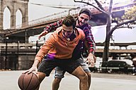 USA, New York, two young men playing basketball on an outdoor court - UUF09126