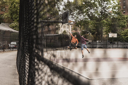 Two young men playing basketball on an outdoor court - UUF09132
