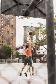 USA, New York, two young men playing basketball on an outdoor court - UUF09135