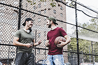 Two smiling friends with basketball outdoors - UUF09144