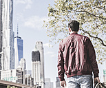 USA, New York City, back view of man looking on Manhattan - UUF09153