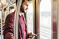 Young man in subway wearing headphones - UUF09159